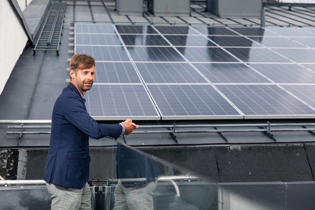 Stiftelsens fastighetschef Mika Soinio står på Aurigas tak och beundrar solpanelerna