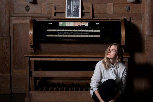 Anna-Maria Marjamäki sitter på huk framför en orgel